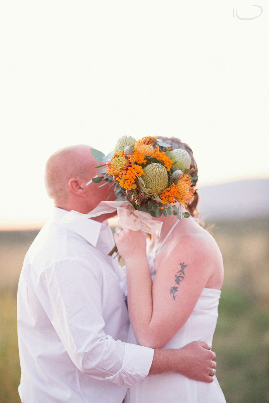 Uluru Wedding Photography: Kissing behind bouquet