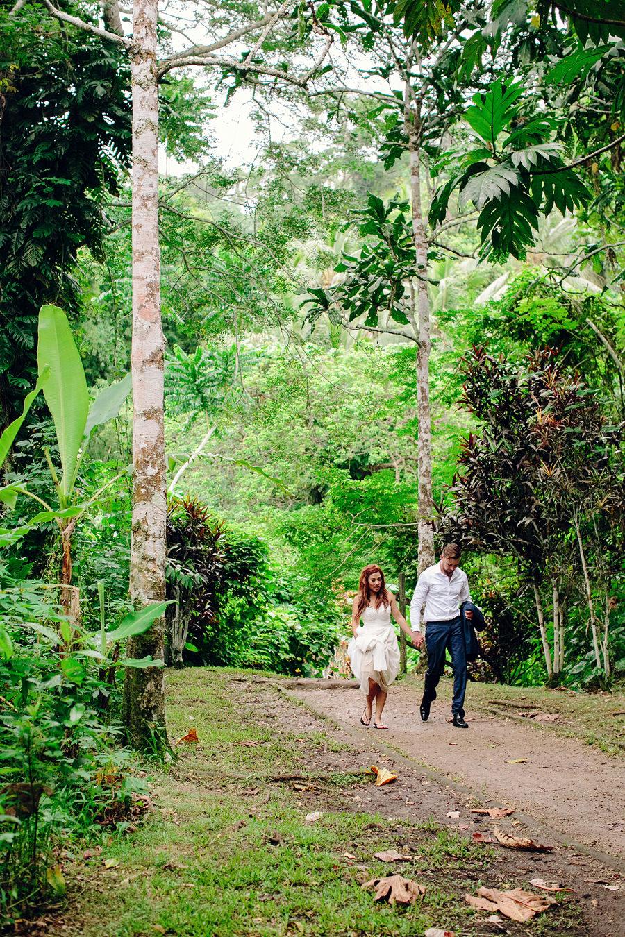 Mele Cascades Vanuatu Wedding Photographers: Bride & groom walking through forest