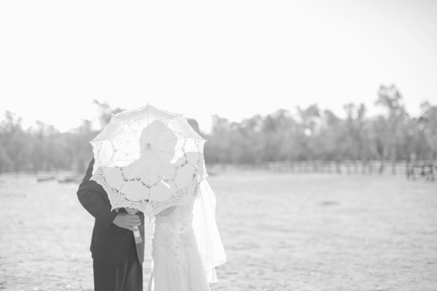 Alice Springs Wedding Photographer: Bride & groom kissing behind parasol